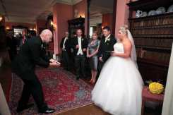 David Fox performing magic to guests at a wedding reception.