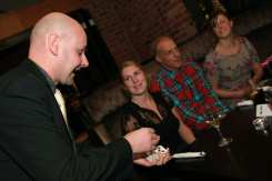 David Fox performing card tricks to guests at a dinner party.